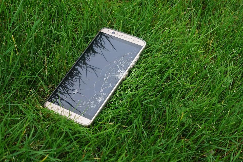 rozbitý mobil v trávě